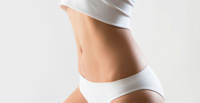 Flat and toned woman in her white under garments
