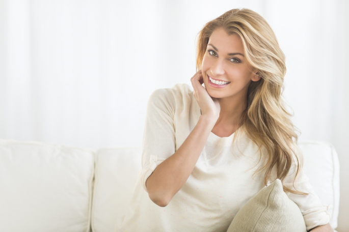 Happy blonde woman posing on living room sofa