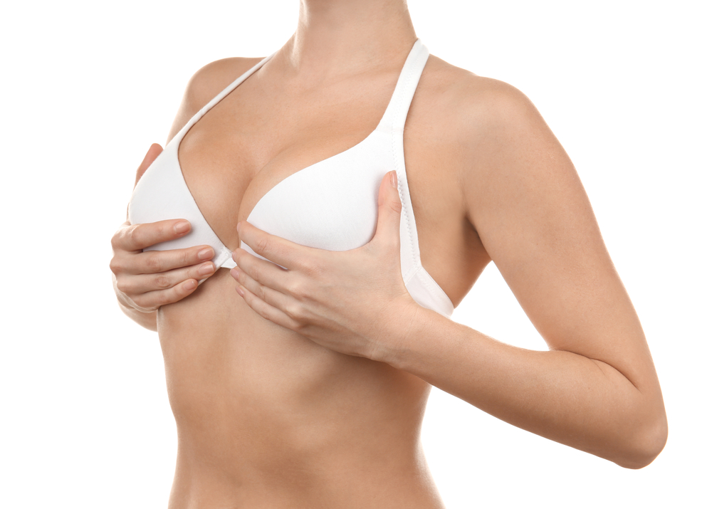 Woman holding her breasts in a white bra