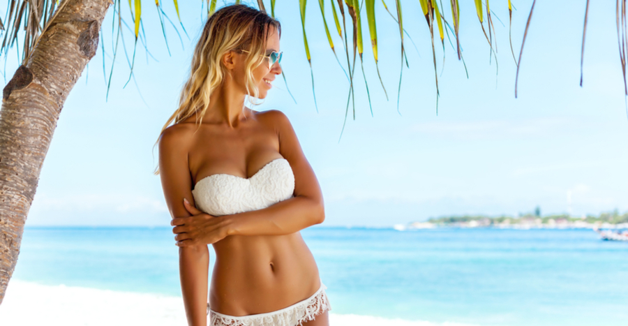 Woman with tasteful augmented breasts in bikini standing on tropical beach