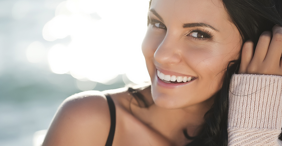 smiling woman with glowing skin from receiving skin care from Greenberg Cosmetic Surgery