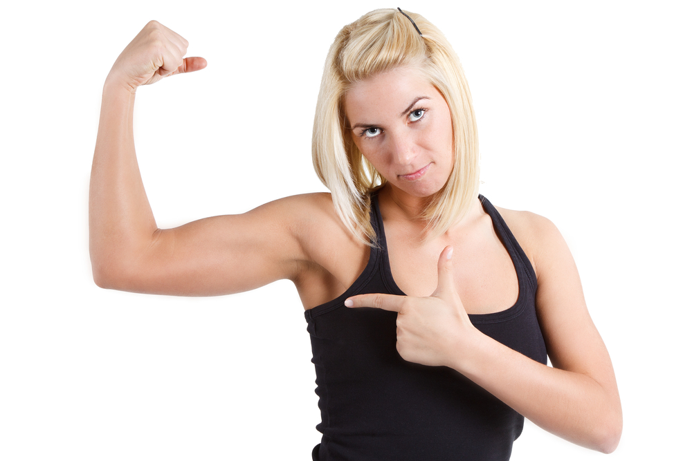 Woman showing off arm definition, flexing bicep