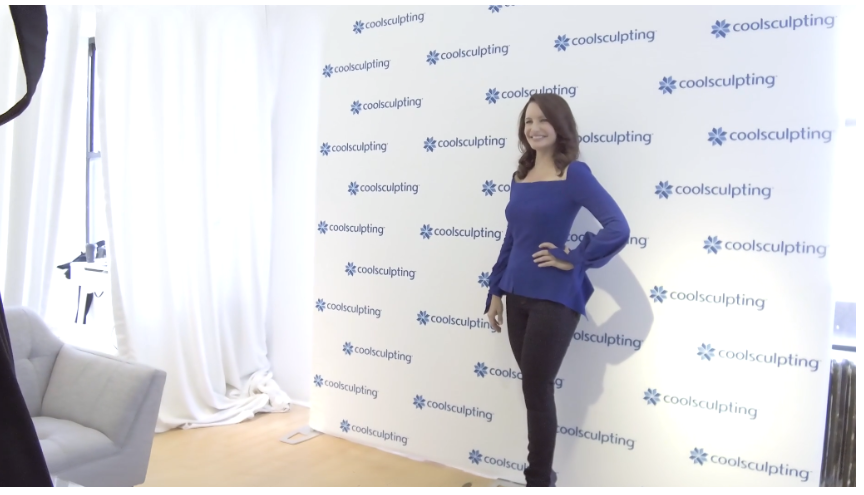 Woman posing infront of cool sculpting backdrop