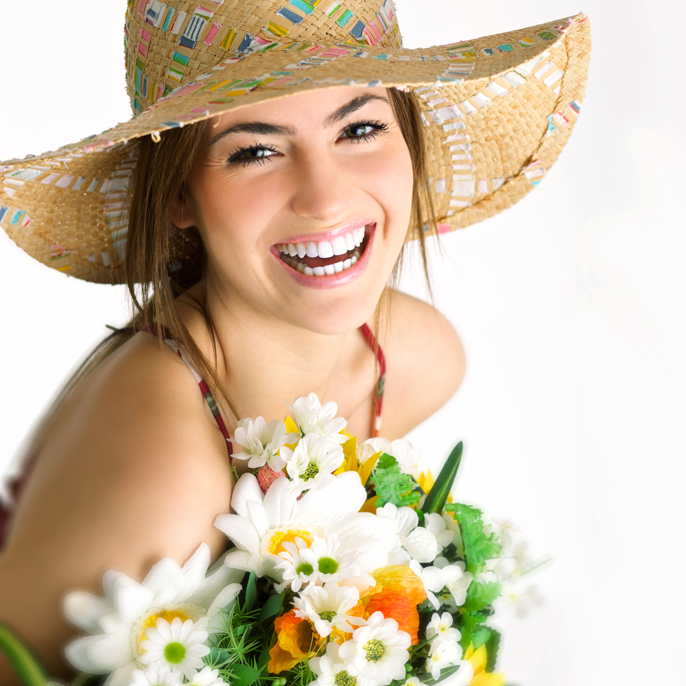 Smiling Girl holding flowers in sunhat